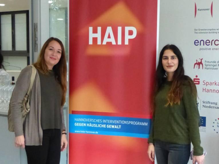 """Zwei Frauen stehen neben einem großen Aufsteller mit der Aufschrift """"HAIP-Hannoversches Interventionsprogramm gegen Häusliche Gewalt""""."""
