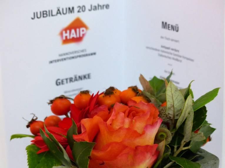 Ein Blumenstrauß mit Rosen und Hagebutten in den Farben des orange-roten HAIP-Logos vor dem aufgeklapptem Programmheft zum 20jährigen Bestehens der Initiative