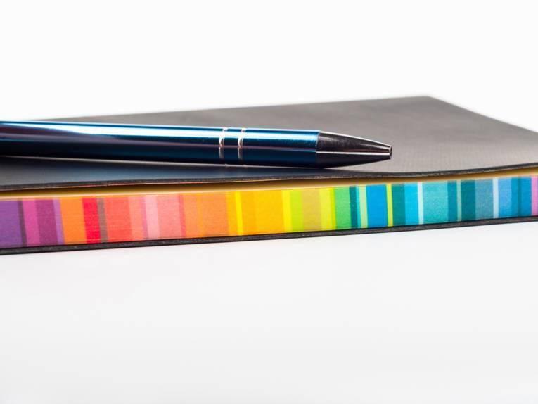 Ein Kugelschreiber liegt griffbereit auf einem farbigen Block