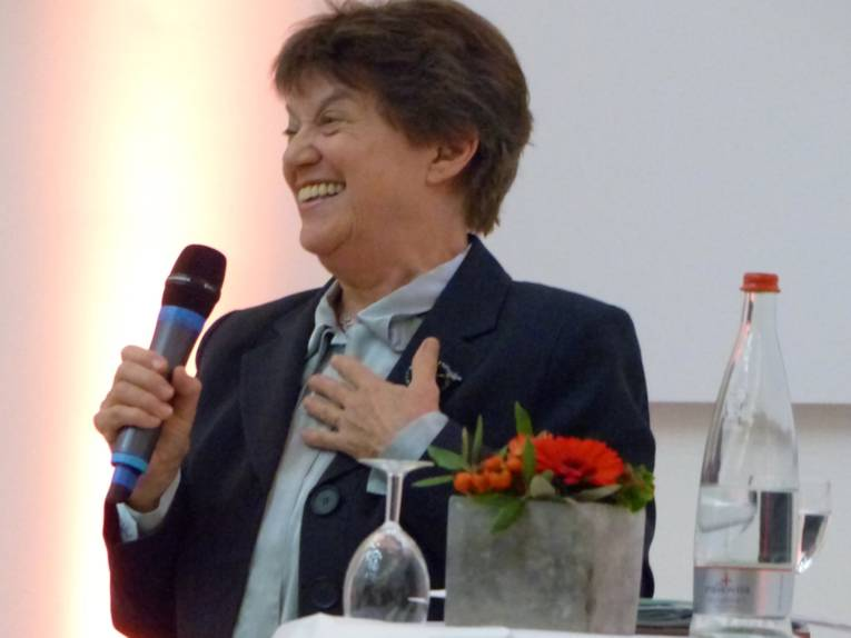 Gastrednerin Prof. Dr. Carol Hagemann-White mit einem Mikrophon am Rednerpult
