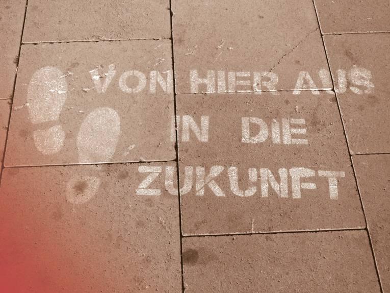 """Auf einem gepflasterten Weg sind zwei Fußabdrücke aufgebracht, daneben der Schriftzug """"Von hier aus in die Zukunft""""."""