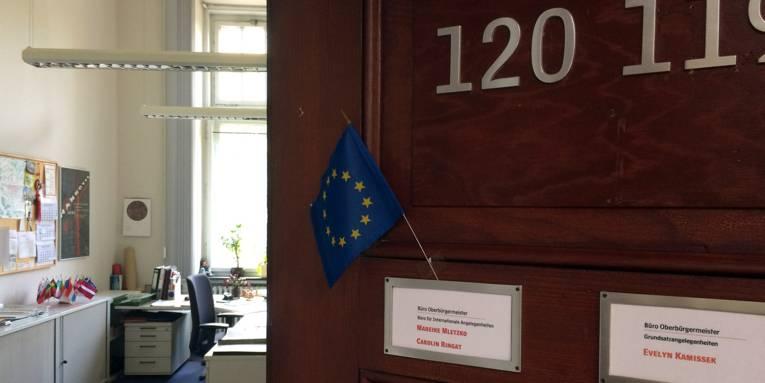 Eine halb offene Bürotür mit einer kleinen Europaflagge am Türschild.