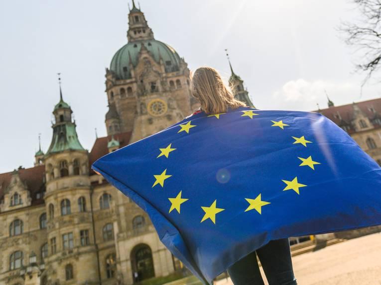 Eine Person steht vor dem Neuen Rathaus und hält eine große Europafahne hoch.