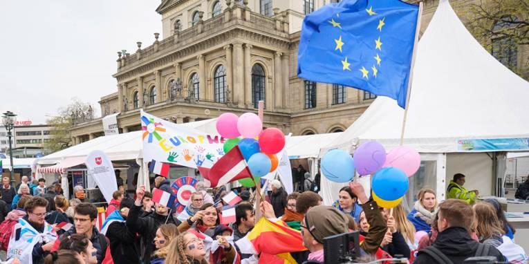 Eine bunte Menschenmenge steht vor der Oper, eine Europafahne wird geschwenkt.