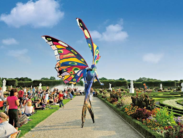 Ein*e Stelzentänzer*in mit bunten Schmetterlingsflügeln auf einem Weg in den Herrenhäuser Gärten, am Rande sitzt Publikum auf dem Rasen.