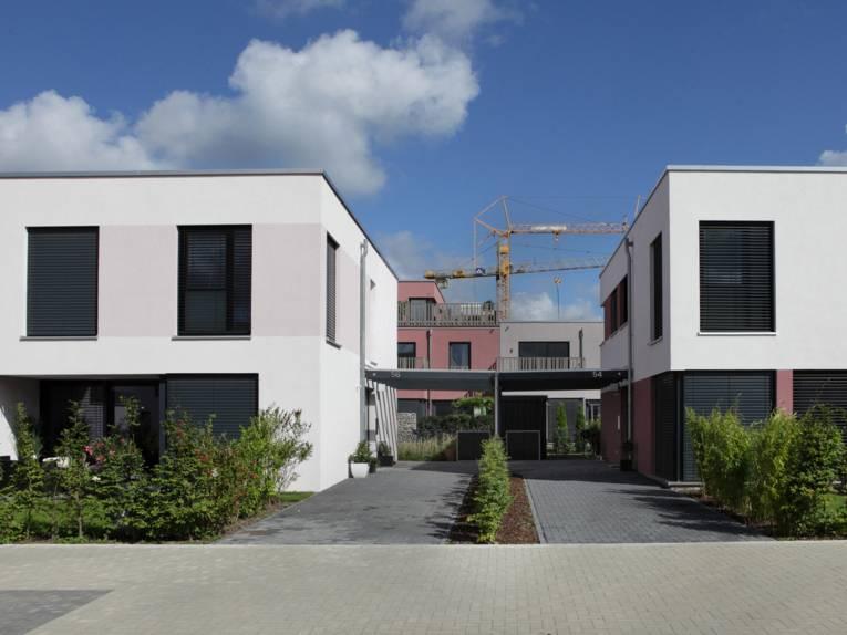 Zweigeschossige Neubauten mit Baukränen im Hintergrund