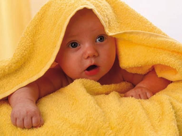 Ein Baby unter einem gelben Handtuch