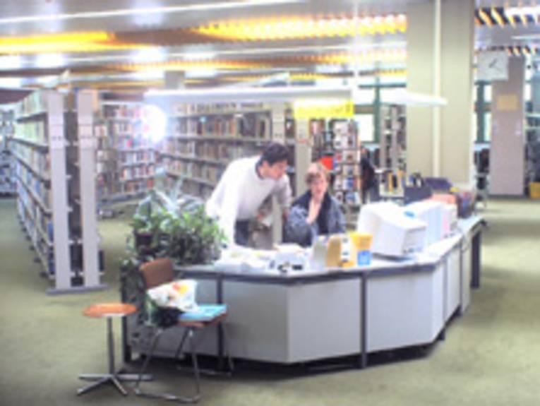 Informationstresen mit einem Mitarbeiter und einer Mitarbeiterin in der Stadt- und Schulbibliothek Bothfeld