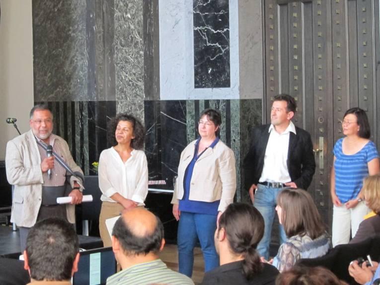 Drei Vertreterinnen und zwei Vertreter von verschiedenen Migrantenorganisationen im Mosaiksaal des Neuen Rathauses