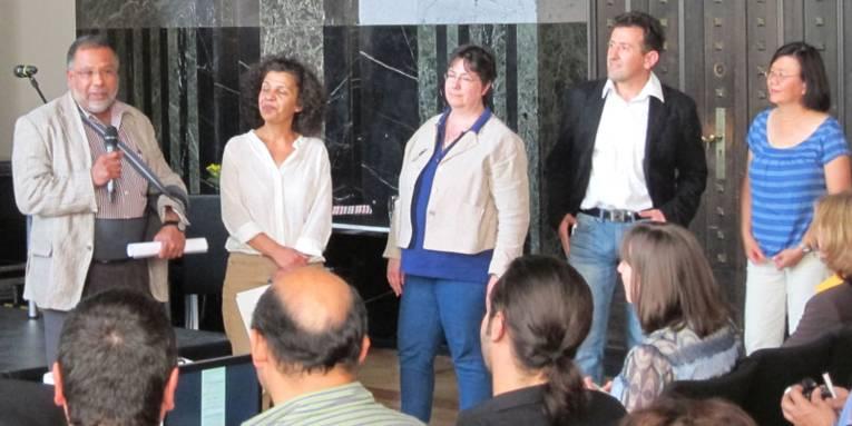 Drei Vertreterinnen und zwei Vertreter von Migrantenorganisationen im Mosaiksaal des Neuen Rathauses