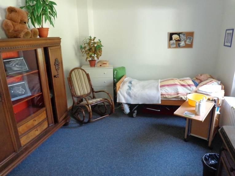 Eine Pflegepuppe in Menschengröße ist zur Nachtruhe gebettet.