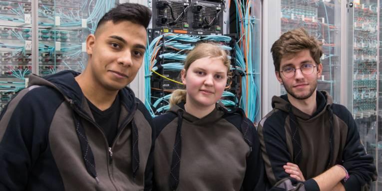 Zwei junge Männer und eine junge Frau stehen in einem Serverraum vor elektronischen Schaltschränken.