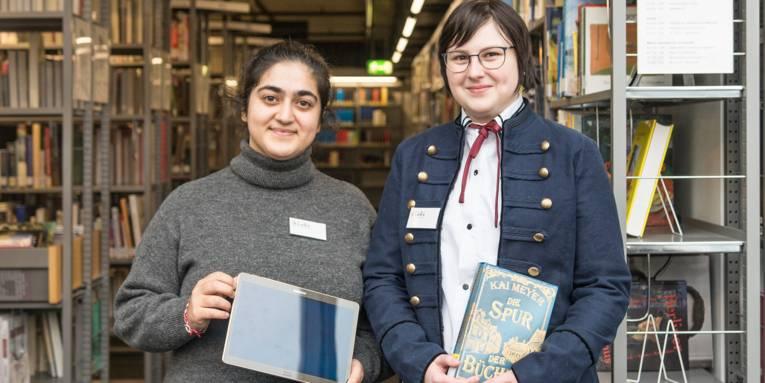 Zwei Auszubildende stehen zwischen Bücherregalen in der Stadtbibliothek; die eine hält ein Touchpad in der Hand, die andere ein Buch.