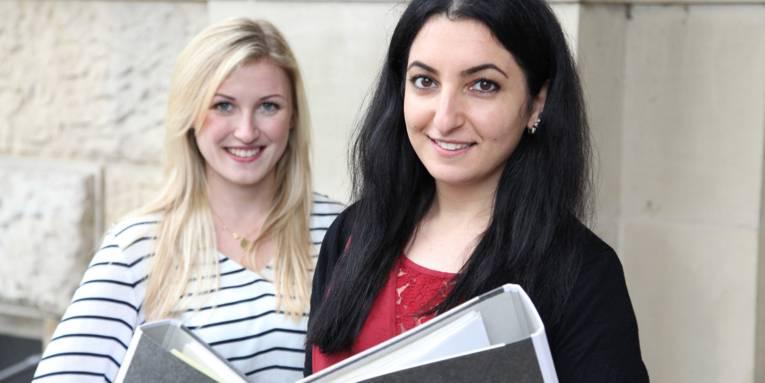 Zwei junge Frauen mit Aktenordnern