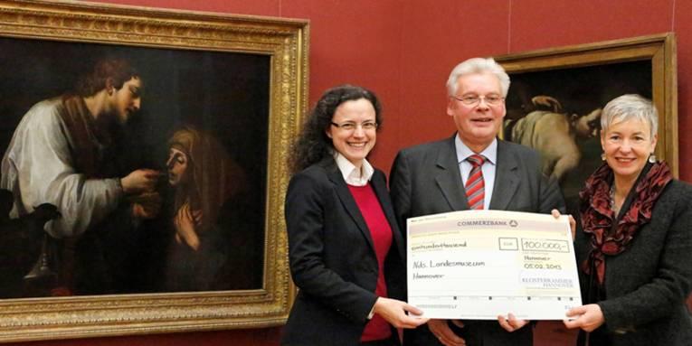 Zwei Frauen und ein Mann halten einen großen Scheck in der Hand.