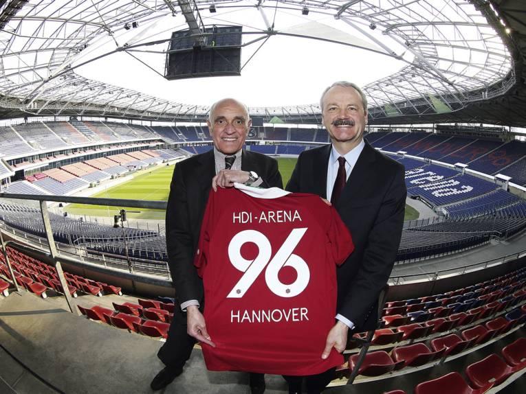 96-Präsident Martin Kind (links) und Dr. Christian Hinsch (stellvertrender Vorstandsvorsitzender der HDI-Gruppe) mit einem 96-Trikot in der Nordkurve der Arena.