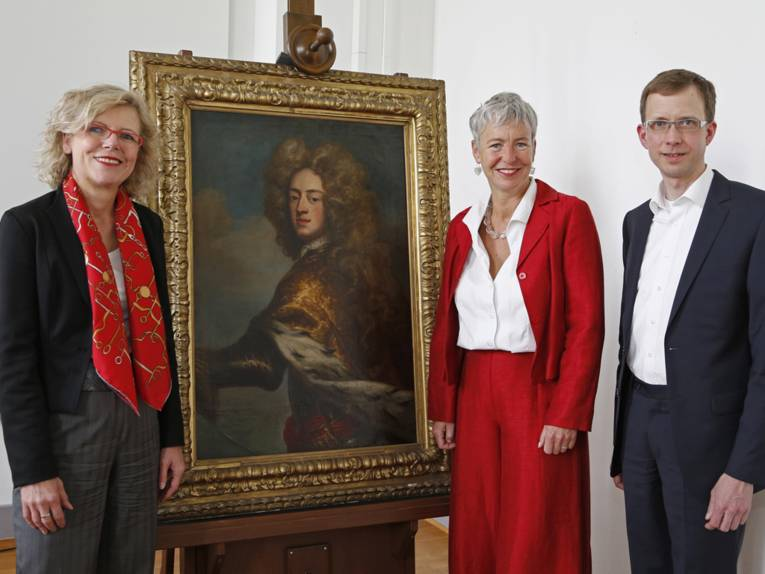 Drei Menschen stehen neben einem Gemälde.