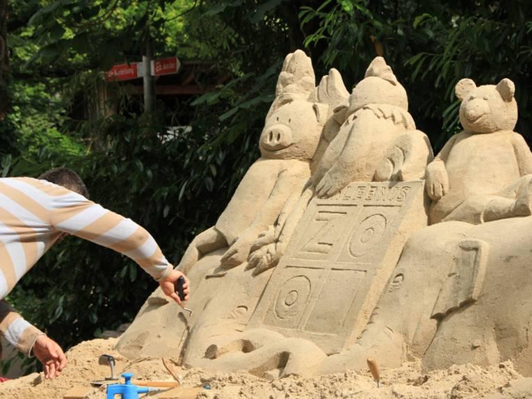 Ein Mann baut eine Sandskulptur.