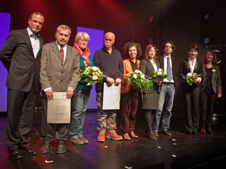 Neun Menschen auf einer Bühne. Zwei tragen eine Urkunde, die Frauen haben Blumensträuße in der Hand.