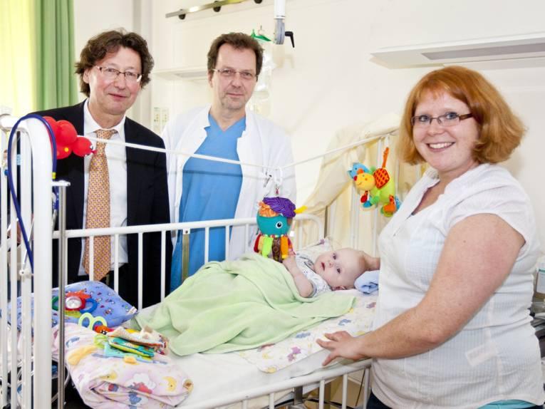 Krankenzimmer mit Säugling und Mutter sowie zwei Professoren.