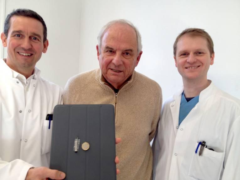 Drei Männer zeigen ein streicholzgroßes Gerät