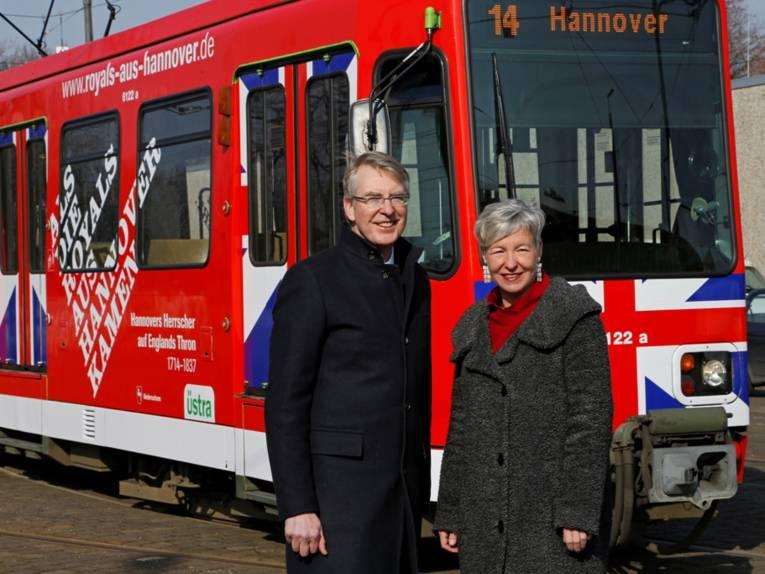 Ein Mann und eine Frau stehen vor einer bunt bemalten Stadtbahn.