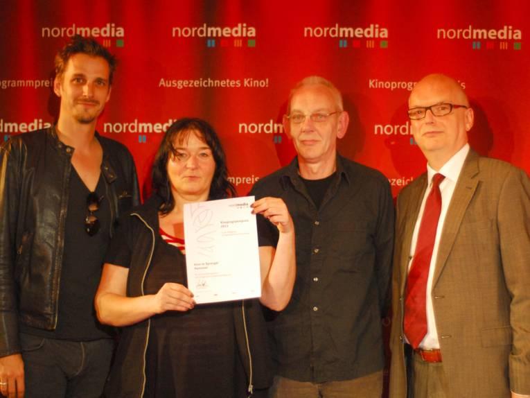 Vier Menschen vor einer roten Wand.
