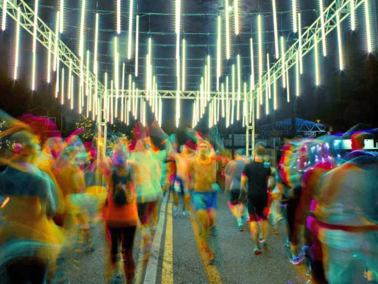 Mit bunten Leuchtmitteln behangene Läufer auf einem beleuchteten Parcours.