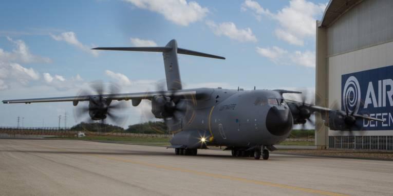Militärisches Transportflugzeug vor Hangar.
