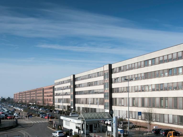 Großes Gebäude mit großer Zahl parkender Fahrzeuge.