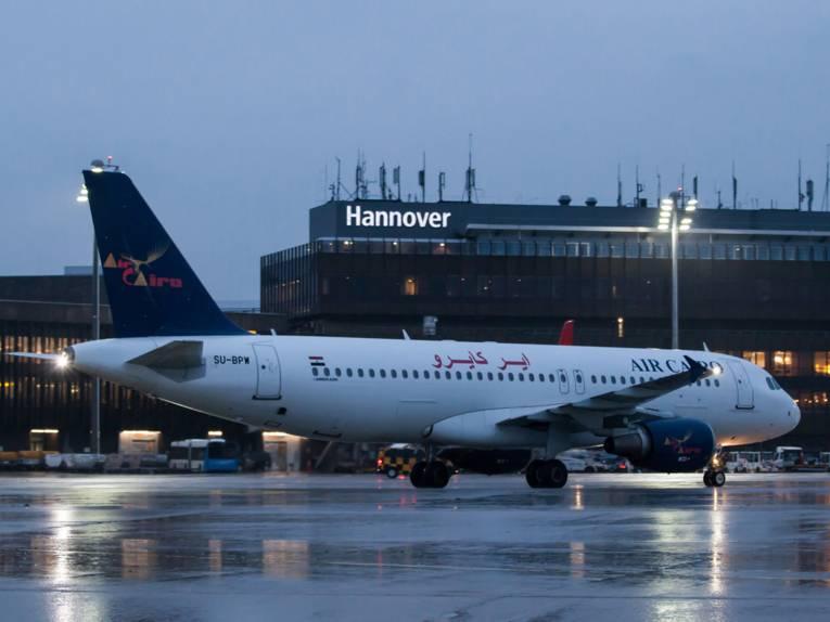 Flugzeug mit arabischen Schriftzeichen vor Flughafengebäude.