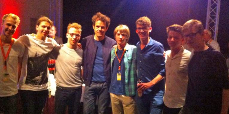 Acht junge Männer stehen auf einer Bühne.