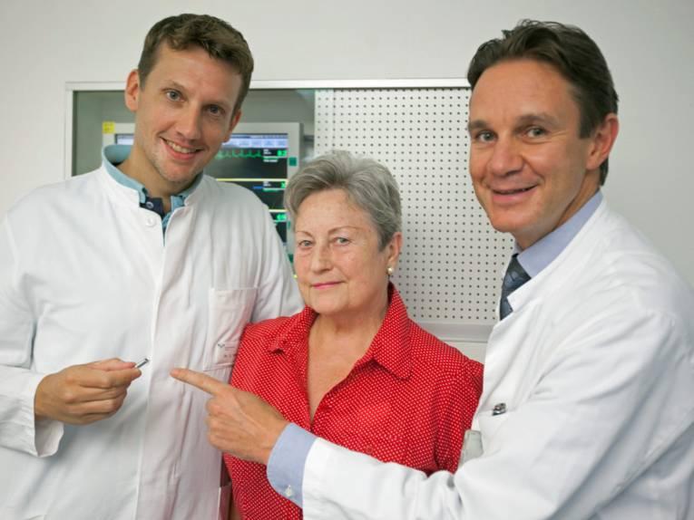 Zwei Ärzte mit einer Frau.
