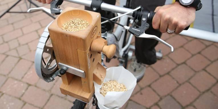 Fahrrad, an dem eine Getreidemühle befestigt ist.