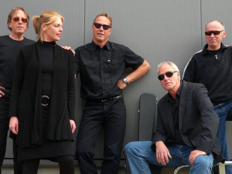 Vier Männer und eine Frau in schwarzer Kleidung.