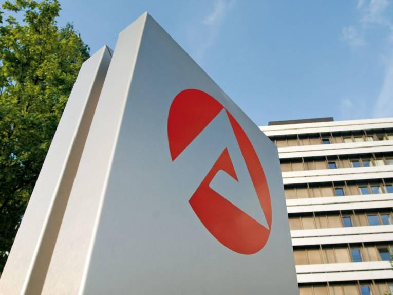 Logo der Bundesagentur für Arbeit auf einer Säule, im Hintergrund ein großes Gebäude.