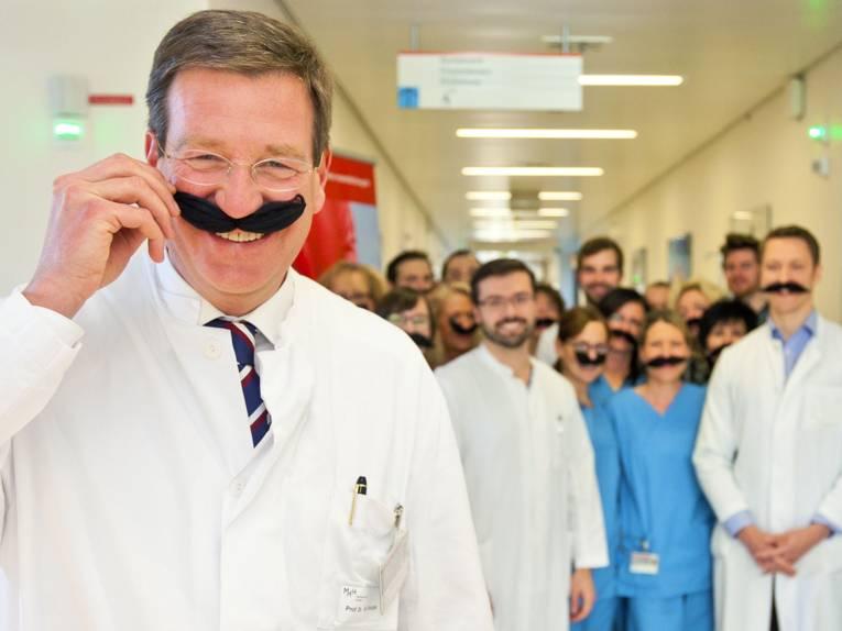 Ein Mann hält sich einen Schnurrbart an, im Hintergrund weitere Menschen mit Schnurrbärten.