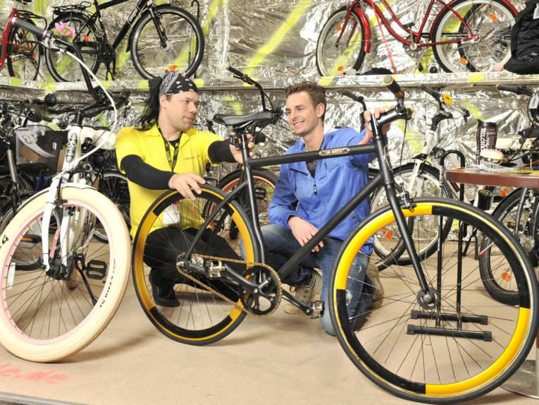 Zwei Männer begutachten ein Fahrrad.