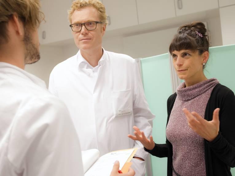 Eine Frau und zwei Männer in Arztkitteln im Gespräch
