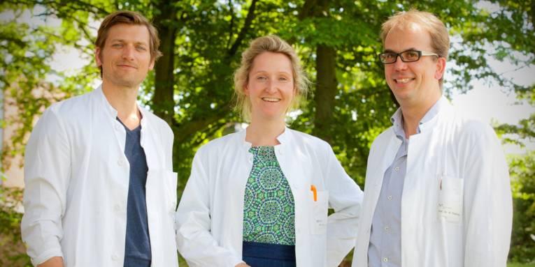 Eine Frau in der Mitte, links und rechts ein Mann. Alle tragen weiße Arztkittel über der Kleidung.