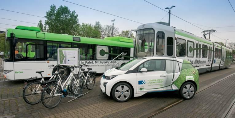 Ein Bus, eine Stadtbahn, ein Auto und vier Fahrräder, die mit ähnlichen Werbemotiven versehen sind.