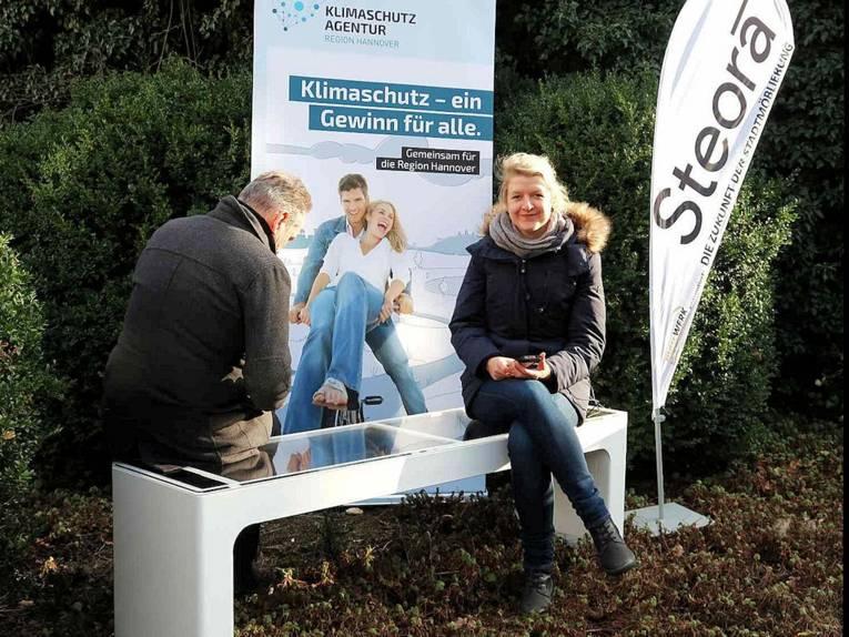 """Ein Mann und eine Frau sitzen auf einer Parkbank vor einem Plakat mit der Aufschrift """"Klimaschutz - ein Gewin für alle."""""""