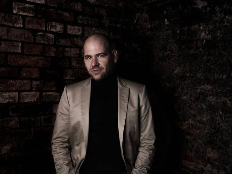 Ein Mann in schwarzem Shirt und hellbraunem Jackett vor sehr dunklem Hintergrund.
