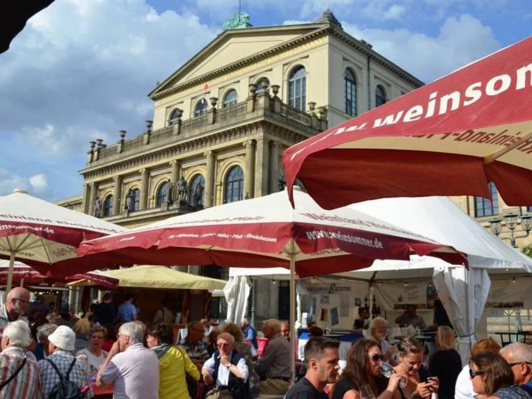Menschen sitzen auf Banken unter Sonnenschirmen auf einem Platz vor einem historischem  Gebäude und trinken aus Weingläsern.