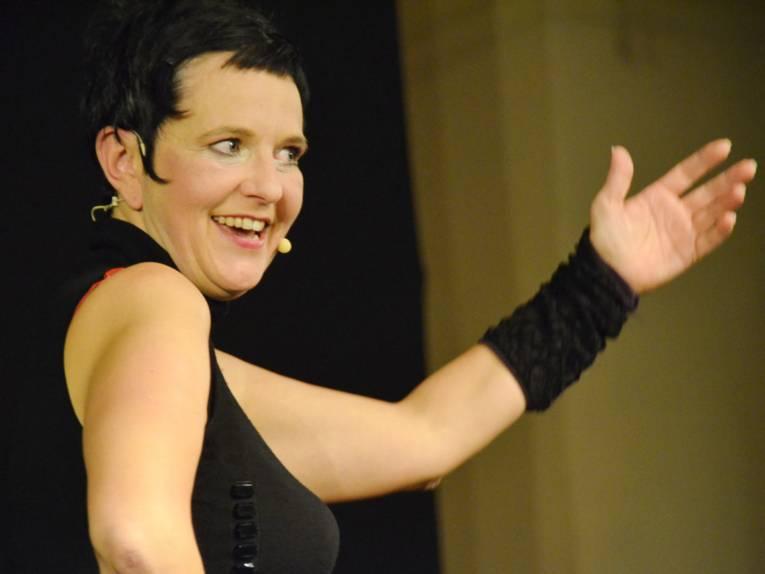 Eine Frau in schwarzen Top mit kurzen schwarzen Haaren.