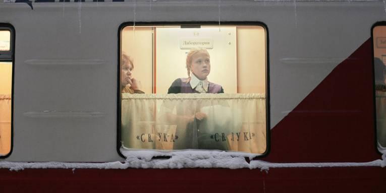 Blick durch ein Fenster in einem Zug, in dem eine junge Frau in einem Gang steht.