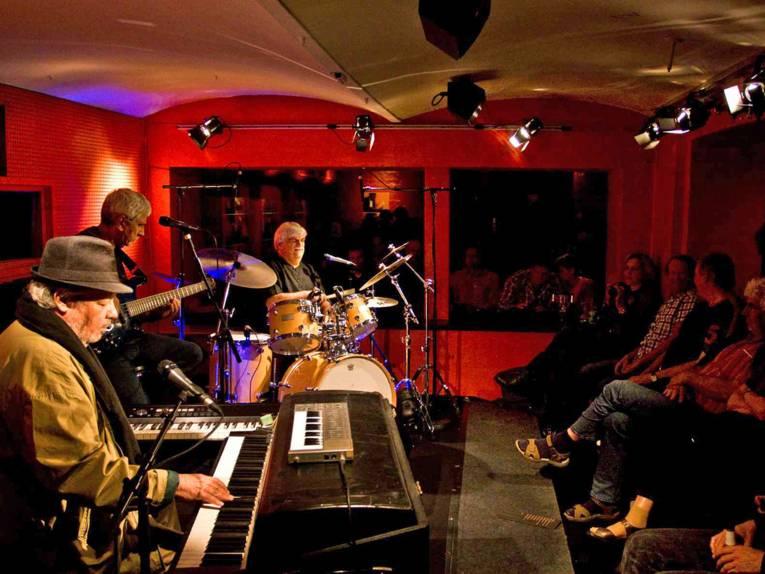 Musiker auf einer Bühne vor Zuschauern auf Stühlen.