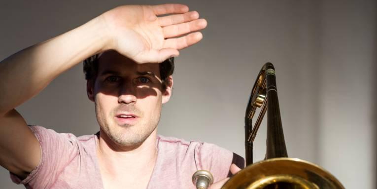 Ein hell angestrahlter Mann beschattet mit einer Hand seine Augen, neben ihm ist ein Teil von einer Posaune zu sehen.