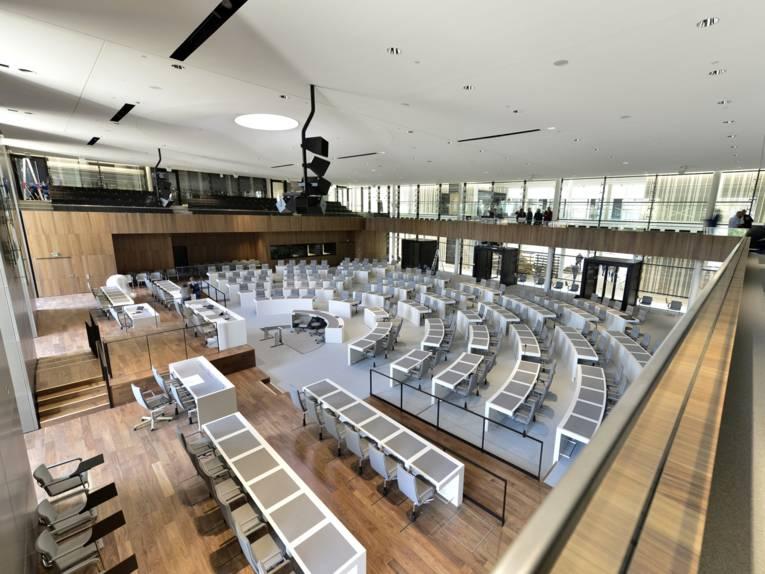 Blick in einen Saal, in dem Stuhlreihen in einem Halbrund angeordnet sind.