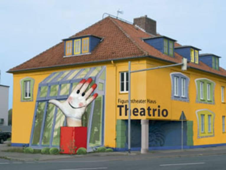 Ein buntes Haus mit einer großen Skulptur in Form einer Hand davor